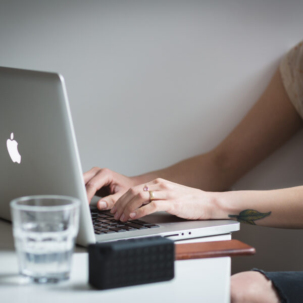 person typing on a Mac laptop